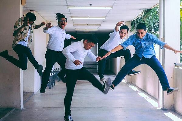 5 men who work within the SAP industry, jumping for joy in an outdoor corridor because their SAP Basis roles are understood.